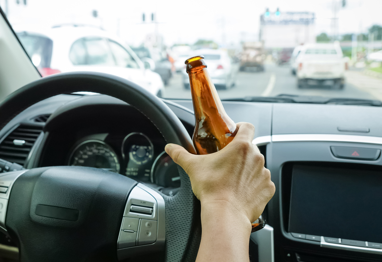 A driver holding alcoholic bottle while driving